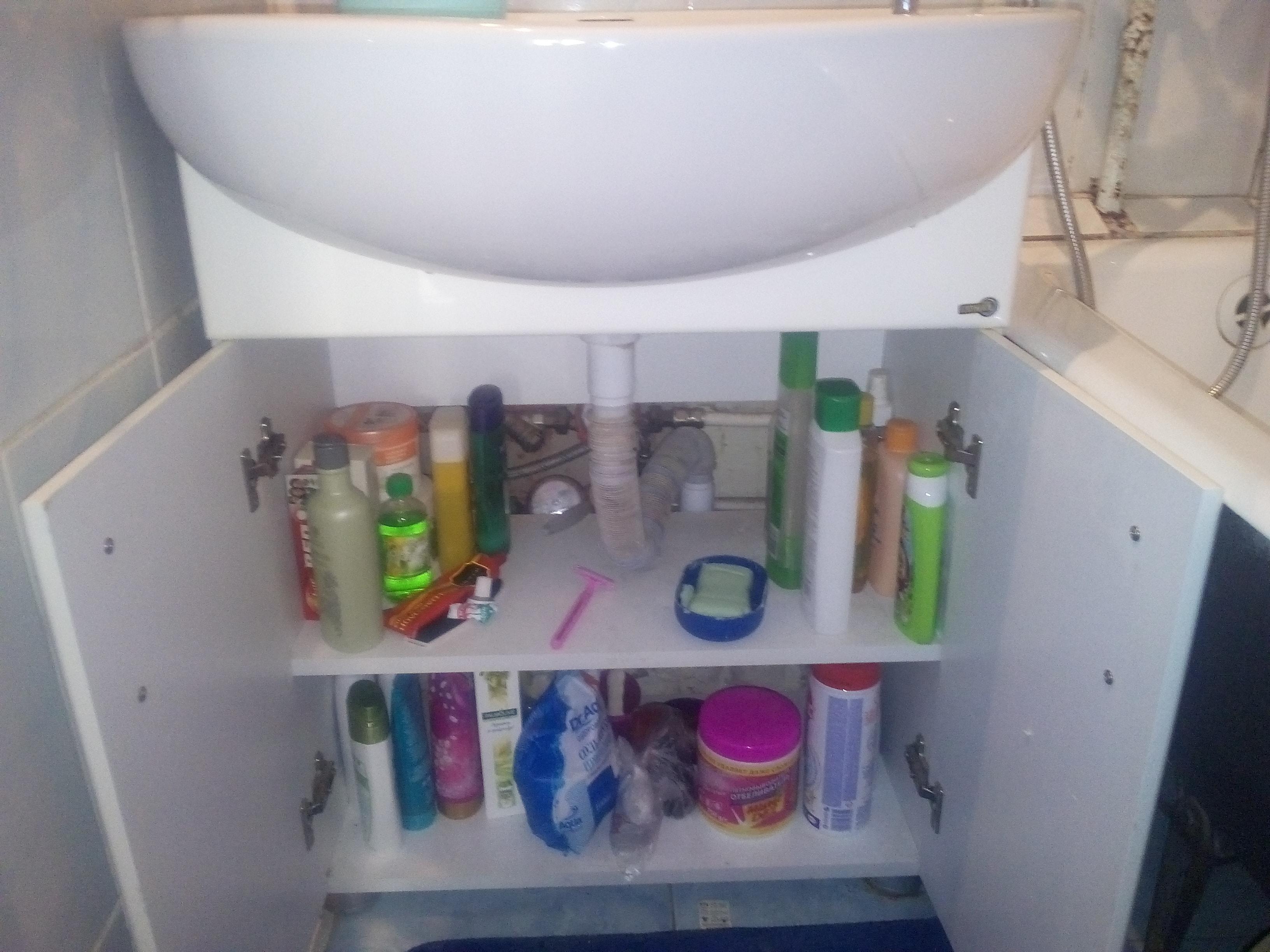 Туалетные принадлежности и бытовая химия в тумбе раковины
